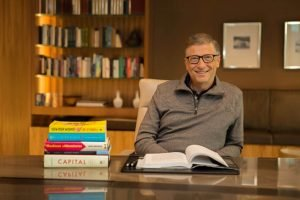 Bill Gates at desk reading a book