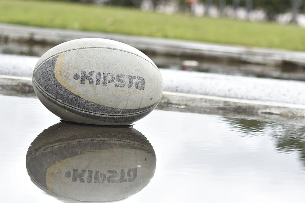 A rugby ball lying in a puddle